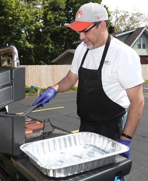Andy McVan grills hot dogs for the Bethany United Church of Christ as the church volunteer group celebrates its 30th year of providing a community meal Saturday, May 15, 2021 in Cuyahoga Falls, Ohio.