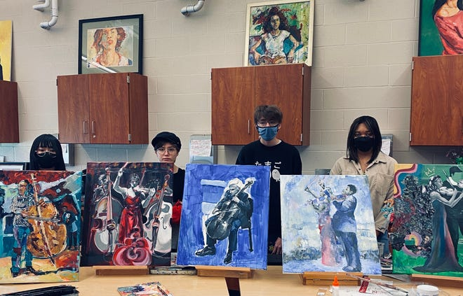 Firestone art students Jenny Wei, from left, Evelyn Brooks, Rowan Loesch and Kamiyah Edwards created paintings inspired by Sphinx Virtuosi Quintet, which will perform May 26 for Tuesday Musical. At far left is a painting by art teacher Patrick Dougherty, who is not pictured.