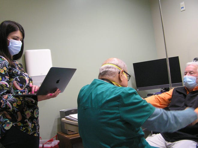 Medical College of Georgia student Keelie Denson takes notes as Dr. Michael Rivner assesses ALS patient Daniel Patterson, 63, at the ALS Clinic at AU Health System.