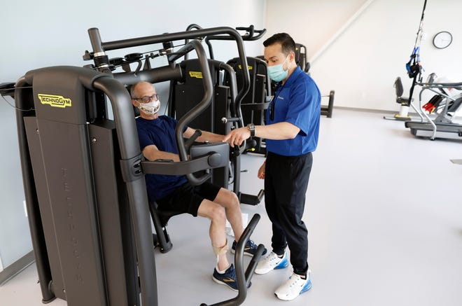 Tyler Yee, right, works with Tim Burns, left, on how to work the new fitness equipment Monday inside the new OhioHealth Neuroscience Wellness Center.