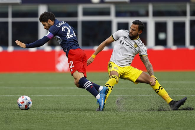 May 16, 2021; Foxborough, Massachusetts, USA; New England Revolution midfielder Carles Gil (22) is tripped by Columbus Crew midfielder Artur (8) during the first half at Gillette Stadium. Mandatory Credit: Winslow Townson-USA TODAY Sports