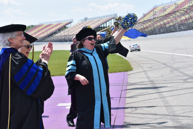 Sister Sharon Weber, O.P., vice president of academic affairs at Siena Heights University, clapping at left, and Cheri Betz, dean of graduate and professional studies at Siena Heights University, waving a pom-pom, cheer as Siena Heights University Class of 2021 graduates receive their diplomas Sunday on the racetrack of Michigan International Speedway.