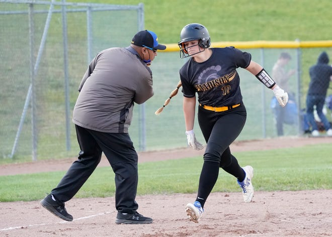 Madison senior Lexi Holtz (10) is congratulated by coach Bill Flores after hitting a home run in a TCC doubleheader against Sand Creek on May 5.