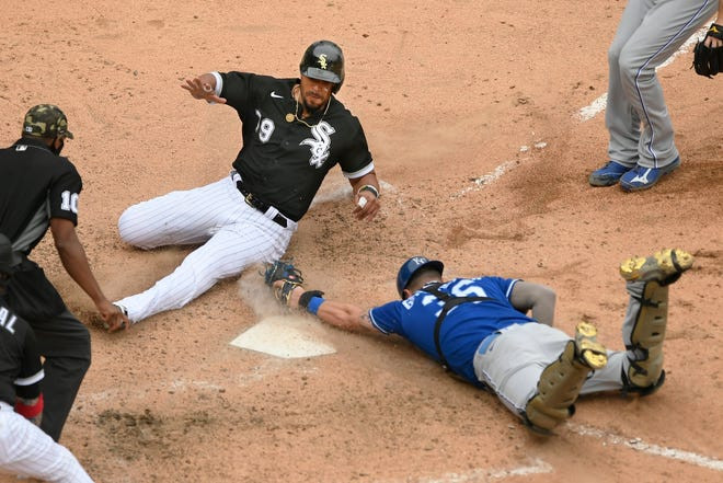 Chicago White Sox's Jose Abreu (79) slides safely into home plate on a wild pitch while Kansas City Royals catcher Cam Gallagher attempts to apply the tag in the bottom of the ninth inning in Sunday's game in Chicago. Umpire Edwin Moscoso, left, ruled Abreu safe for the winning run in Chicago's 4-3 victory and video replay said thete was not enough evidence to overturn the call.