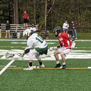 Oakmont's Evan Thibault (10) scoops up a ground ball  at midfield in front of Hudson's Ivan O'Neil during last Thursday's game at Arthur I. Hurd Memorial Field in Ashburnham.