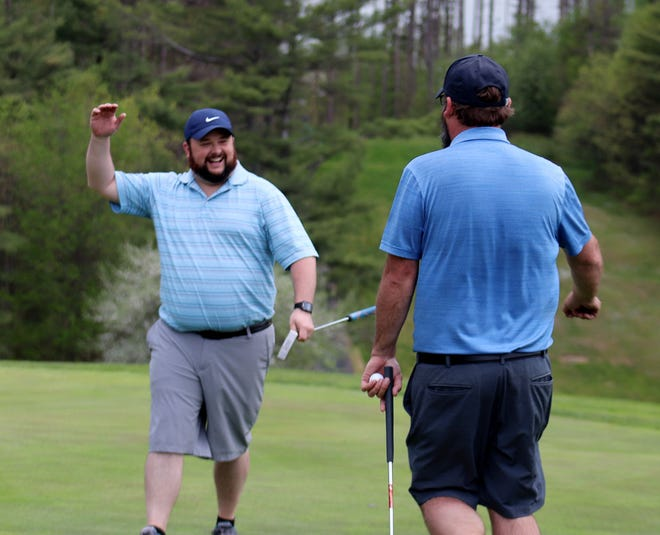 Brandon Wightman, left, moves in for a high five from teammate Ryan Pasakinskas after Pasakinskas made the winning putt in the annual Spring Member-Member championship, Sunday, at Gardner Municipal Golf Course.