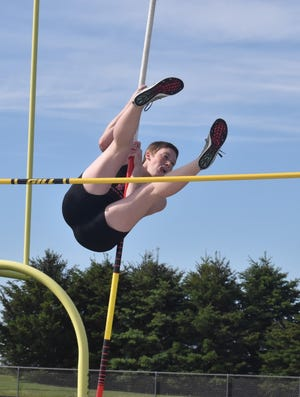 Charger Kileigh Burge sticks out her tongue as she goes over the bar in the pole vault on Tuesday, May 11, at Charger Field. Orion competed with Morrison.