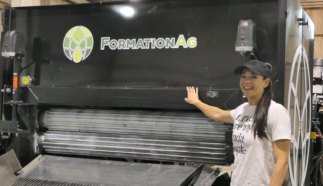 Melissa Nelson co-owner of South Bend Industrial Hemp shows off a new piece of equipment in their Great Bend factory.