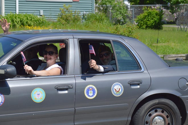 Jolene Constant, left, administrative assistant at the Leominster Veterans' Services office, and veteran Bob Bray, right, wave American flags during the 2019 Memorial Day parade — the last time there has been a Memorial Day parade because of COVID-19. There will be no parade this year as well, but the annual ceremonies will be held throughout Memorial Day weekend.