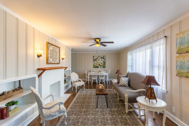 AFTER: Walls painted in Sherwin Williams Modern Gray, a brick fireplace painted off-white, a light-colored area rug over refinished wood floors, and white sheer drapery panels lighten the mood and brighten this living space.