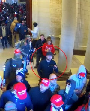 Participants in the storming of the U.S. Capitol on Jan. 6 used mobile devices to organize, document and broadcast many of the events that day. As seen in the red circle in this image taken from a closed-circuit television camera, Tanner Bryce Sells appears to use a cell phone while inside the Capitol.
