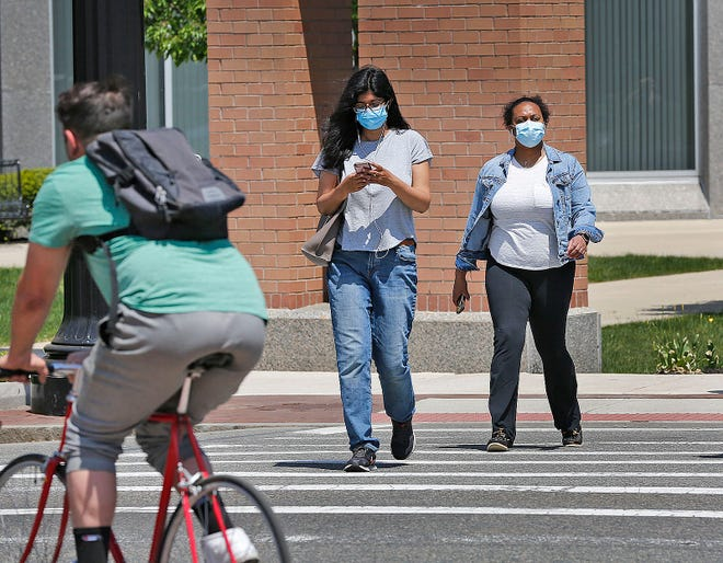 Pedestrians wearing masks cross Hancock Street in Quincy Square on May 17, 2021.