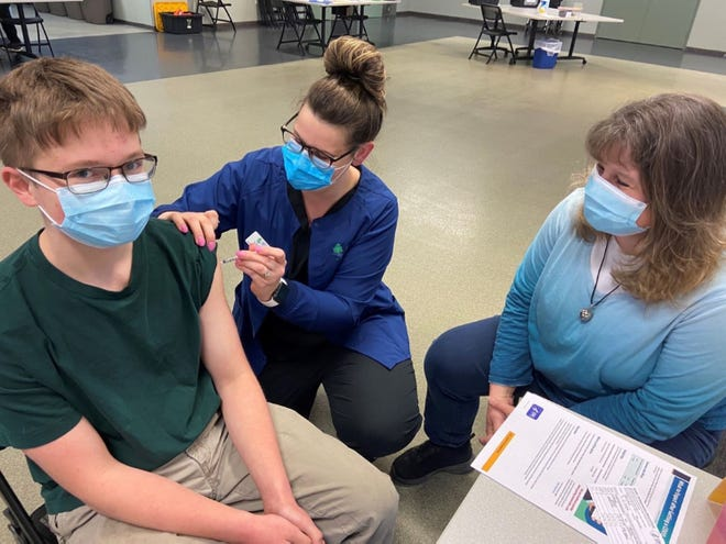 Tommy Skinner, 14, accompanied by his mother Tracy Skinner, received his Pfizer vaccination on May 13 by Vanessa Mushlock, RN at a Health Department of Northwest Michigan clinic at the Emmet County Fairgrounds.