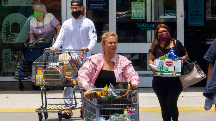 Masked and unmasked customers leave the ALDI store on Okeechobee Boulevard in West Palm Beach Monday, May 17, 2021. The store still has a sign on the door requiring masks.
