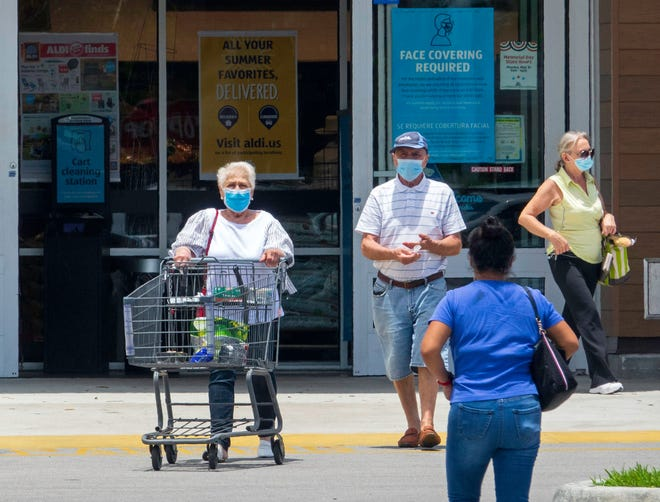 Customers wearing masks leave the ALDI store on Okeechobee Boulevard in West Palm Beach Monday, May 17, 2021. The store still has a sign on the door requiring masks.