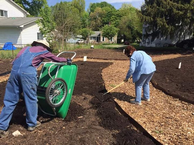 Karl Liske and Nancy Warlop of the Kent Environmental Council work on spreading mulch at the Thomas-Anderson Memorial Garden in Kent's historic South End.