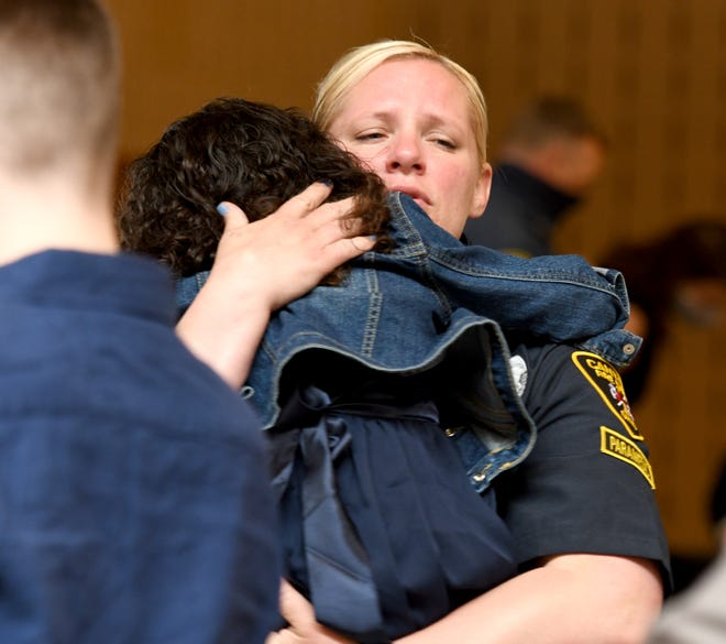 Lauren Gilkison hugs daughter Kori Copeland, 3, after getting sworn in as a member of Canton Fire Department during a ceremony Monday at Canton Civic Center.