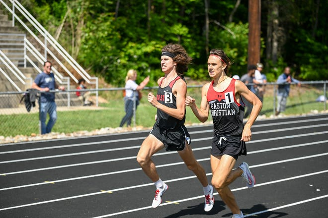Coastal Christian's Nick Scrocco (left) prepares his finishing move in his title-winning 800 meter run at the NCISAA Division II State Championships.
