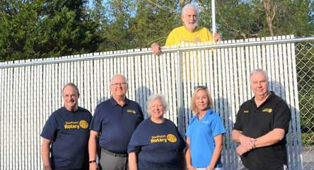 Volunteers help repair a fence  for Hope Harbor Home, a shelter for domestic violence victims, in 2018.