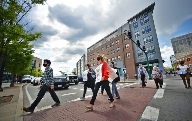 """The group crosses the road leading to the hub as they march to the hub for a """"fare free WRTA"""" Monday."""