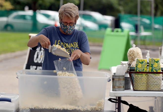 Wendie Mitchell, with Midway Kettle Corn and Lemonade, fills a bag of kettle corn for a customer during the Reynoldsburg Farmers Market on June 4, 2020. The market returns June 10 at John F. Kennedy Park, 7232 E. Main Street, andwill run each Thursday through Aug. 26.