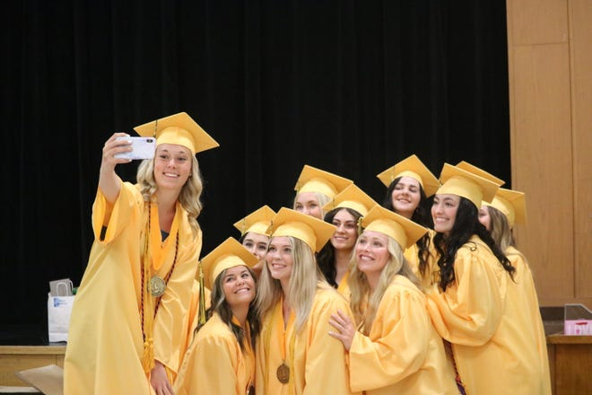 Roncalli High School graduate Anna Schmidt takes a group photo with some of her classmates. Roncalli's graduation was Sunday.