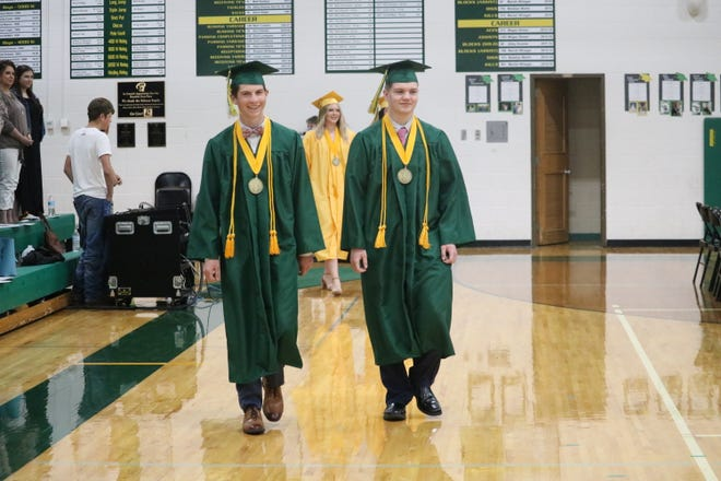 Roncalli graduates John Reynen and Dawson Brandner process into gym Sunday afternoon.