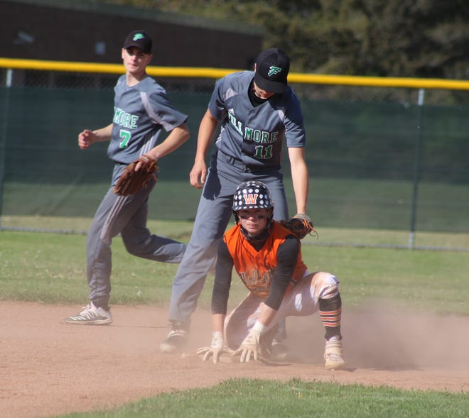Wellsville's Alex Ordiway slides safely back into second base as Fillmore's Isaiah Voss applies the tag Monday night.