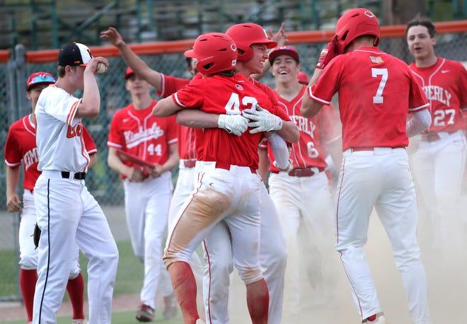 Kimberly's Colin Obermann (42) is hugged by Mason Stepanski (19) and swarmed by teammates after hitting a three-run home run against Kaukauna on May 14 in Kaukauna.
