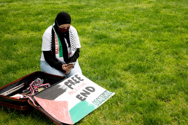 Amira Hasan, of Hamilton, sits next to her sign while protesting Israeli aggression against Palestinians at Washington Park in Over-The-Rhine on Sunday, May 16, 2021.