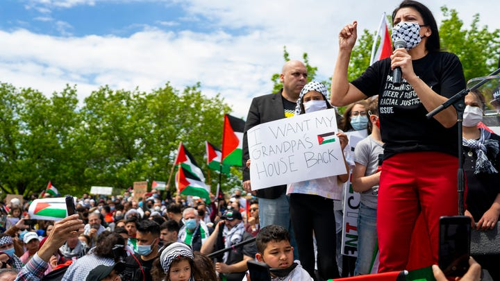 Rashida Tlaib, right, (U.S. Representative for Michigan's 13th congressional district) speaks during a rally in support of Palestine held by New Generation for Palestine on Sunday, May 16, 2021, in Dearborn. Tlaib spoke about the injustices Palestinians face and critiqued President Biden for his support of Israeli forces. She also addressed the efforts of herself and The Squad (a group of six Democratic members of the U.S. House of Representatives) in congress to further Palestinian human rights.