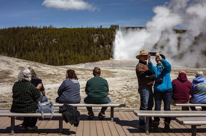 Tourists watch Old Faithful erupt in Yellowstone National Park on Thursday, April 29, 2021, in Wyoming.