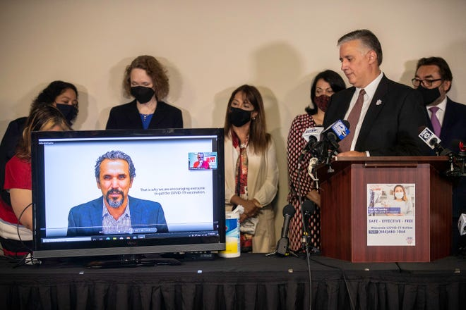 Forward Latino President Darryl Morin watches a commercial produced by the organization at a news conference on Monday announcing a campaign to boost vaccinations in the state's Latino population.
