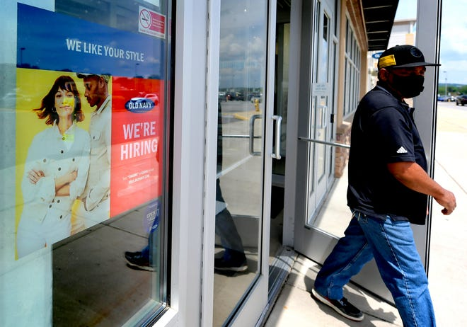 A patron exits Old Navy at Manchester Crossroads, passing a sign advertising for employees Monday, May 17, 2021. Bill Kalina photo