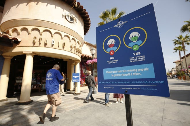 Signage encourages guests to use proper protection as Universal Studios Hollywood welcomed back people in April. (Al Seib/Los Angeles Times/TNS)
