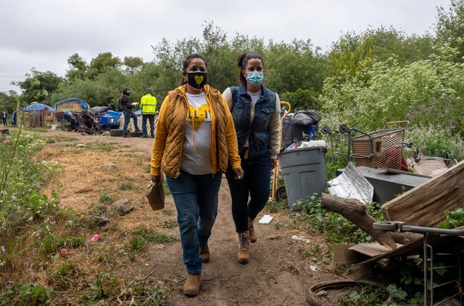 Two All-In Monterey members walk through a homeless encampment during a mobile COVID-19 vaccine clinic in Salinas, Calif., on Friday, May 14, 2021.