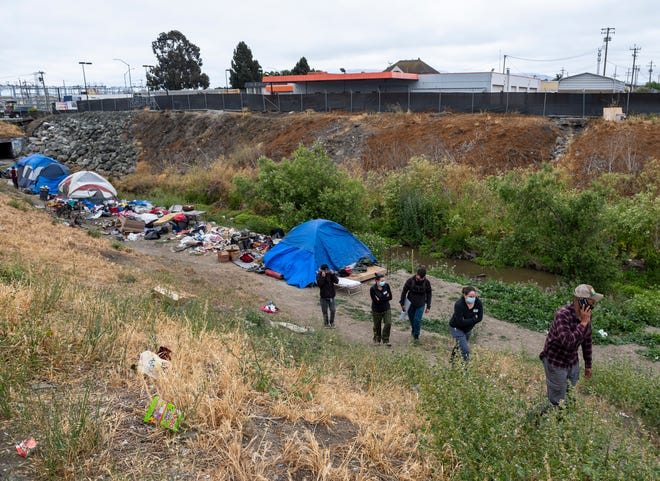 Members of Central Avenue Pharmacy, All-In Monterey, and the Center for Community Health Engagement walk up from a homeless encampment in Salinas, Calif., on Friday, May 14, 2021.