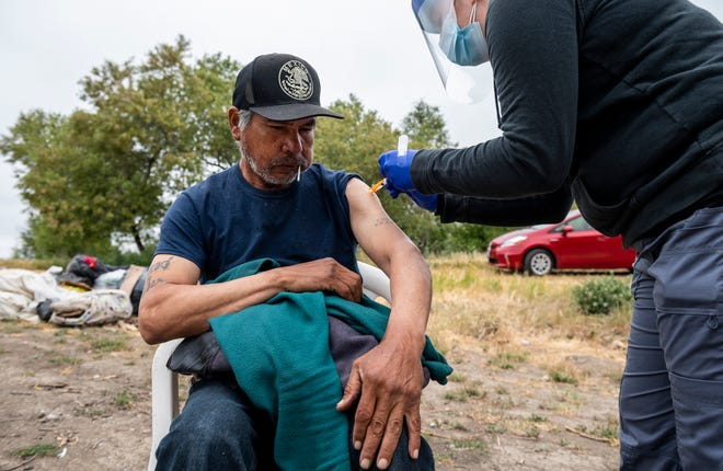 A person experiencing homelessness gets their Johnson & Johnson vaccine during a mobile vaccination clinic hosted by Central Avenue Pharmacy, All-In Monterey, and the Center for Community Health Engagement in Salinas, Calif., on Friday, May 14, 2021.