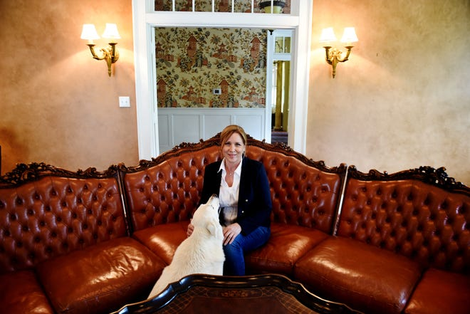 Cindy Wilkinson with her clients' dog on the semicircular couch that will be for sale at the upcoming estate sale.