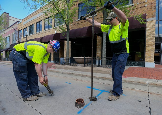 Ray Younger (left) and Floyd Smith (right) turn off a water main valve Monday on Washington Street in front of the Wausau Center mall. Demolition is expected to begin later this week.