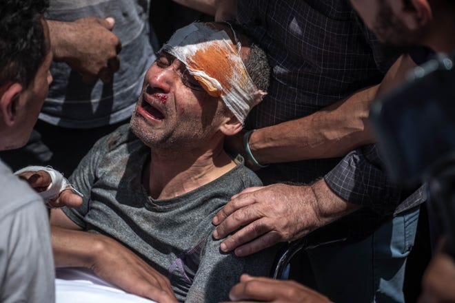 A Palestinian survivor mourns his children who were killed in a violent Israeli raid in the central Gaza Strip on May 16, 2021 in Gaza City, Gaza.