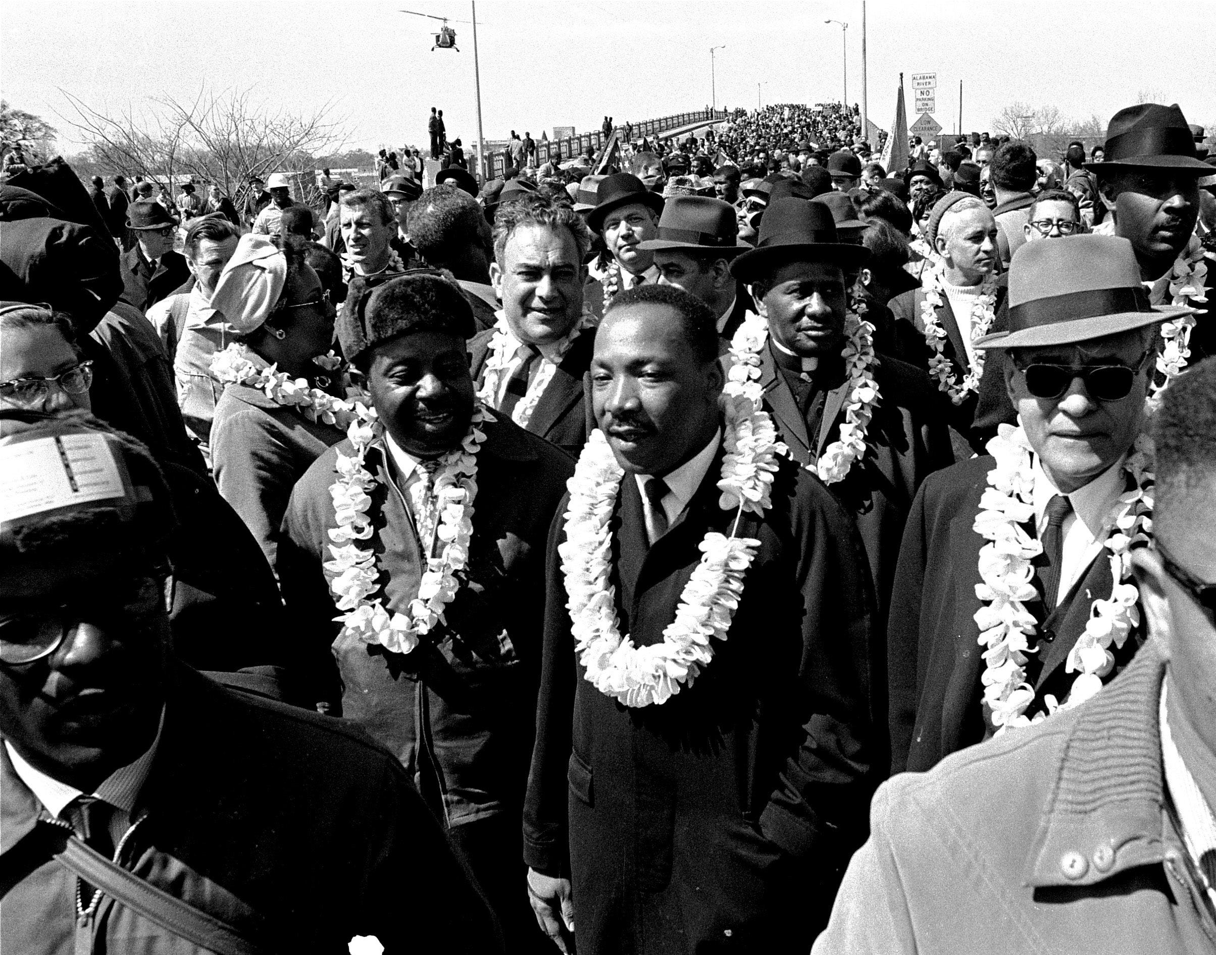 In this March 21, 1965 file photo, Martin Luther King, Jr. and his civil rights marchers cross the Edmund Pettus Bridge in Selma, Ala., heading for capitol, Montgomery, during a five day, 50 mile walk to protest voting laws.