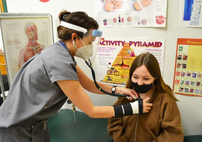 West Ridge Middle School nurse Jennifer Trombley works with a student. Nurses' duties during the pandemic include contacting family and staff when students report symptoms, contact tracing for elementary students, and conducting followup with positive cases.