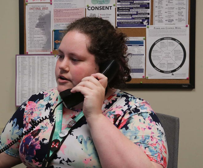 Shannon Pritchard, a crisis intervention specialist, takes calls Tuesday on the hotline at the Battered Women's Shelter of Summit & Medina Counties in Akron. The shelter and other agencies that assist victims are facing more cuts in federal funding.