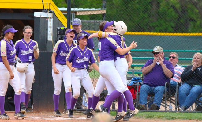 Maddie Redman (left) and Myah Johnson (right) hug after Johnson scores on a wild throw in Game 2 of the Plains District title at East Park on Monday. Butler won the game 21-4.
