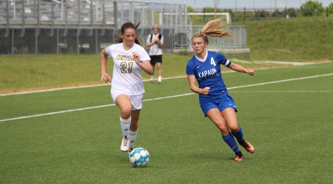 Andover Central's Mary Metz (21) and Kapaunt Mount Carmel's Eden Hadley (4) fight for a ball at Stryker Soccer Complex in Wichita, Kansas on Monday, May 17.