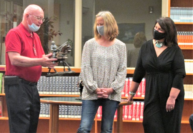 nterim West Holmes Superintendent John Thomas presents a Knight statue to retiring personnel Karen Hunter and Nancy Miller at the school board meeting Monday in the West Holmes High School Library.