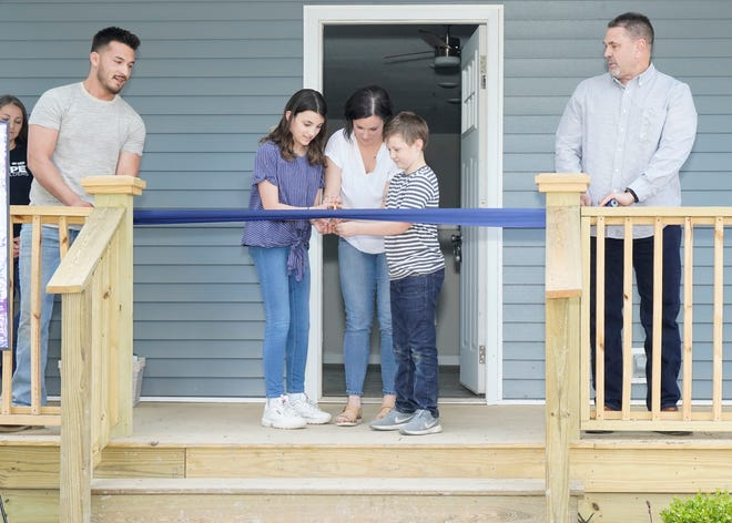 Emily Newell, an Adrian mother of two, cuts the ribbon with her children, Tegan, 12, left and Elijah, 8 while Caleb Nieto, site manager for Habitat for Humanity of Lenawee County and Doug Straub, construction manager for Habitat for Humanity of Lenawee County hold the ribbon during Sunday's Faith Build dedication event in Adrian.