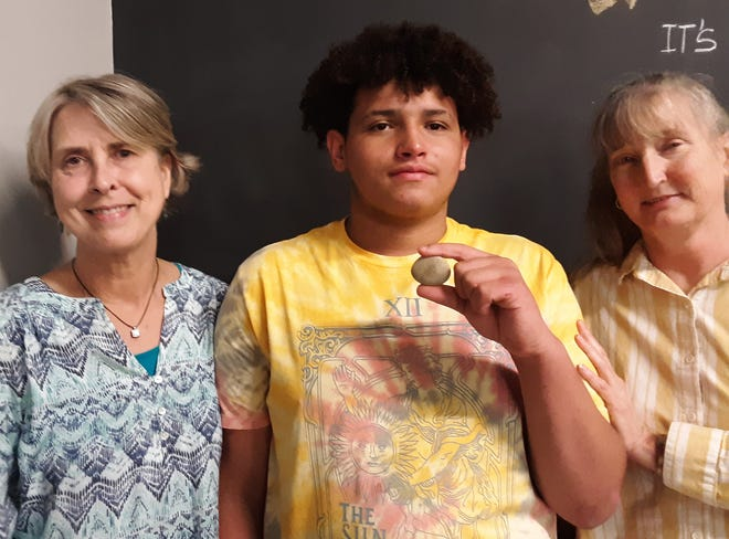 Deviyoun Williams displays a rock he received from two of his former teachers representing rough edges smoothed away during a ceremony to celebrate his completion of a law literacy program. Also pictured are Lisa Childress (left) and Ms. Donna McMahan.