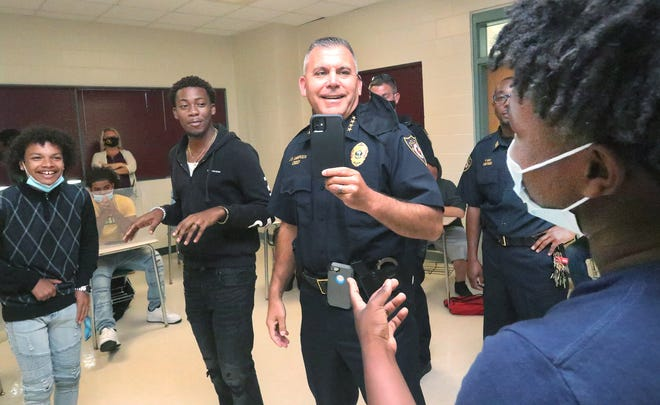 Student Tristan Colon, left, laughs while DeLand Police Chief Jason Umberger, playing the role of a teenage driver with a carload of pals, takes cellphone video during a mock traffic stop, with DeLand High student Santear Johnson, at right, playing an officer, Monday, May 17, 2021, during a Conversations with Police lunch at the school. One of several topics discussed during the meeting was building trust between young men and police.
